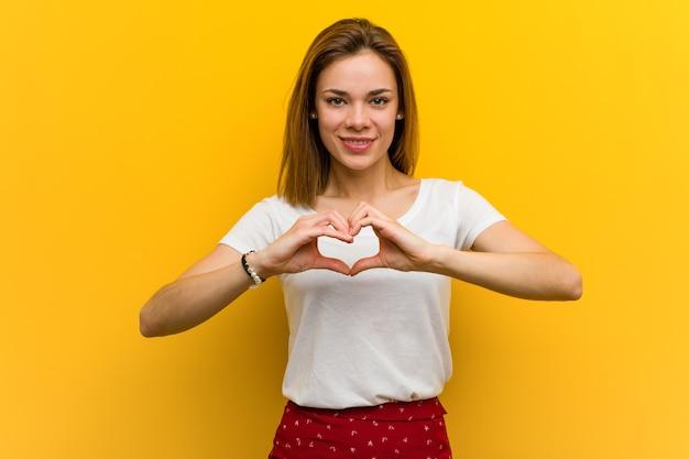 Jovem mulher caucasiana natural sorrindo e mostrando uma forma de coração com as mãos.
