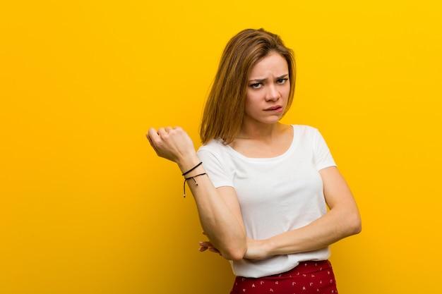 Jovem mulher caucasiana natural tocando a cabeça para trás, pensando e fazendo uma escolha.