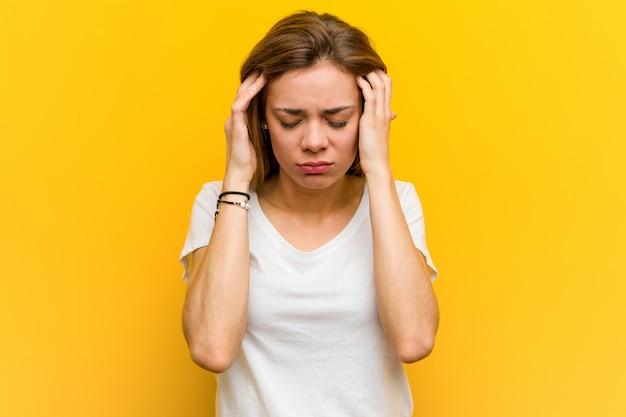 Jovem mulher caucasiana natural tocando seus templos e tendo dor de cabeça.
