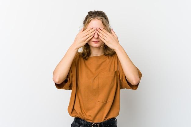 Jovem mulher caucasiana no backrgound branco com medo de cobrir os olhos com as mãos.