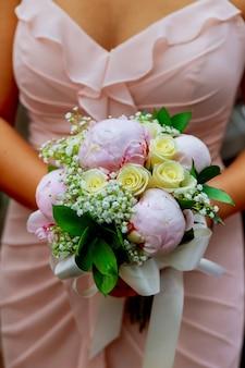 Jovem mulher caucasiana no vestido de renda rosa detém um buquê
