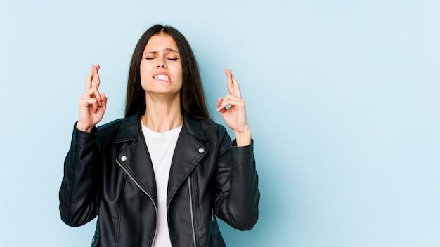 Jovem mulher caucasiana nos dedos de cruzamento de parede azul