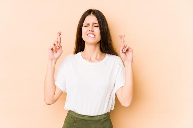 Jovem mulher caucasiana nos dedos de cruzamento de parede bege por ter sorte