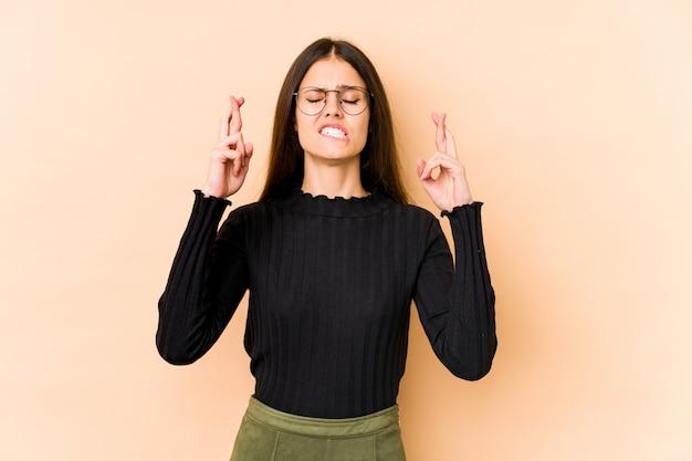 Jovem mulher caucasiana nos dedos de cruzamento de parede bege