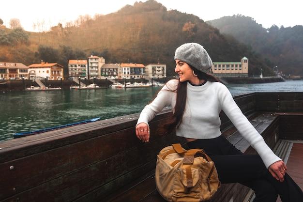 Jovem mulher caucasiana, olhando para a baía de pasaia, no país basco.