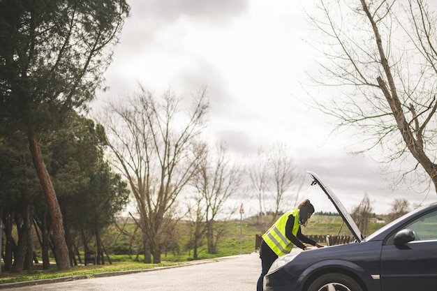 Jovem mulher caucasiana, olhando para o motor do carro, carro quebrado no meio da estrada. conceito de assistência automóvel e na estrada.