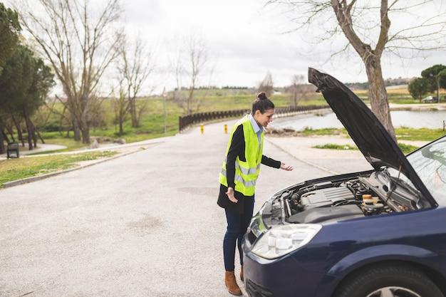 Jovem mulher caucasiana, olhando para o motor do carro, ela não sabe o que fazer, carro quebrado no meio da estrada. conceito de assistência automóvel e na estrada.