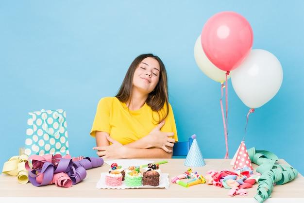 Jovem mulher caucasiana, organizando um abraços de aniversário, sorrindo despreocupada e feliz