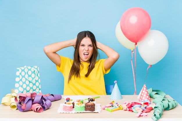 Jovem mulher caucasiana, organizando um aniversário, cobrindo as orelhas com as mãos, tentando não ouvir um som muito alto.