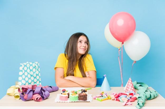 Jovem mulher caucasiana organizando um aniversário e sonhando em alcançar objetivos e propósitos