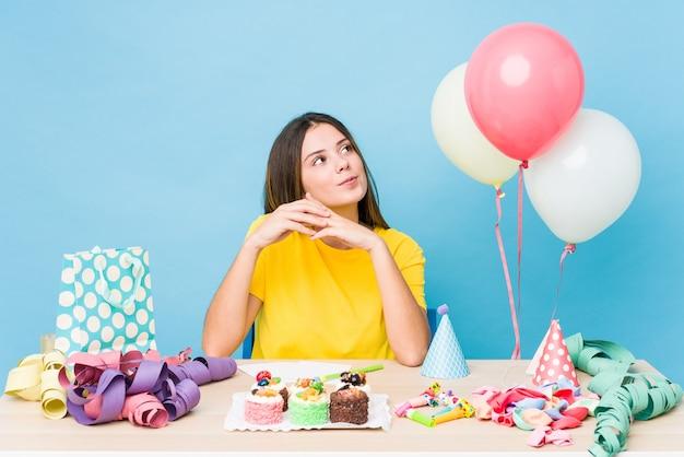 Jovem mulher caucasiana, organizando um aniversário, inventando o plano em mente, criando uma ideia.