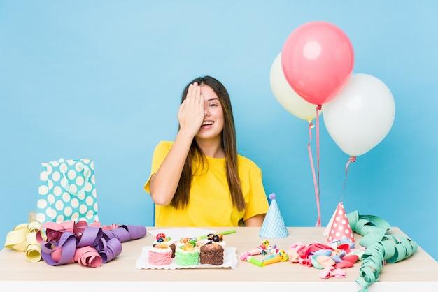 Jovem mulher caucasiana, organizando um aniversário se divertindo cobrindo metade do rosto com a palma da mão.
