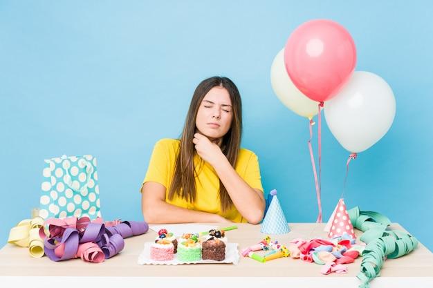 Jovem mulher caucasiana, organizando um aniversário sofre dor na garganta devido a um vírus ou infecção.