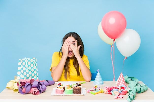 Jovem mulher caucasiana, organizando um piscar de aniversário por entre os dedos assustados e nervosos.