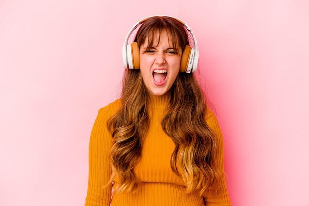 Jovem mulher caucasiana, ouvindo música com fones de ouvido isolados, gritando muito zangado e agressivo.