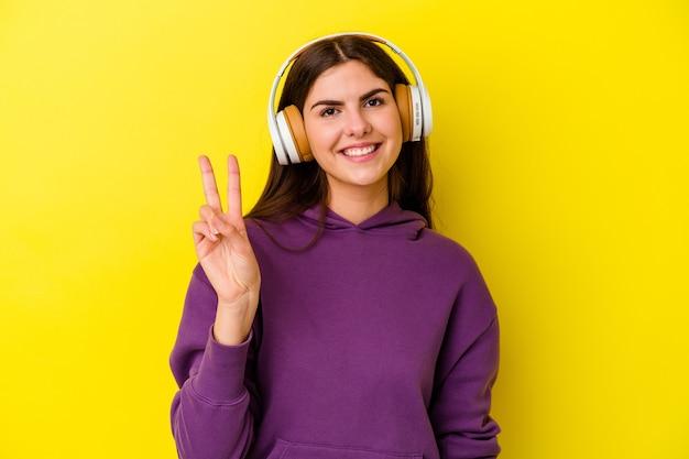Jovem mulher caucasiana, ouvindo música com fones de ouvido isolados na parede rosa, alegre e despreocupada, mostrando um símbolo de paz com os dedos.