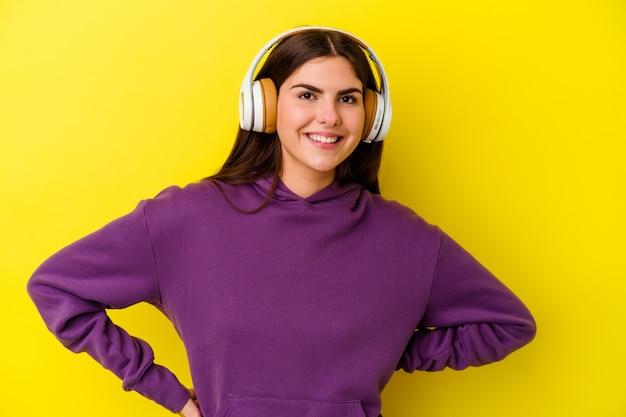 Jovem mulher caucasiana, ouvindo música com fones de ouvido isolados na parede rosa confiante, mantendo as mãos nos quadris.