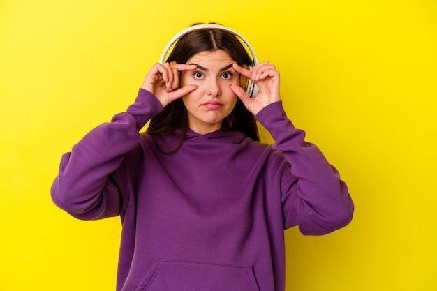 Jovem mulher caucasiana ouvindo música com fones de ouvido isolados na parede rosa, de olhos abertos para encontrar uma oportunidade de sucesso
