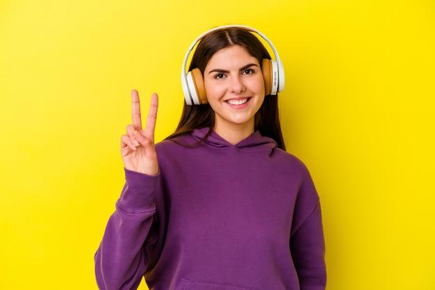 Jovem mulher caucasiana, ouvindo música com fones de ouvido isolados na parede rosa, mostrando sinal de vitória e sorrindo amplamente.