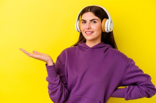 Jovem mulher caucasiana, ouvindo música com fones de ouvido isolados na parede rosa, mostrando um espaço de cópia na palma da mão e segurando a outra mão na cintura.