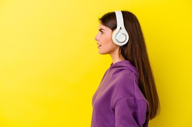Jovem mulher caucasiana, ouvindo música com fones de ouvido isolados na parede rosa, olhando para a esquerda, pose de lado.