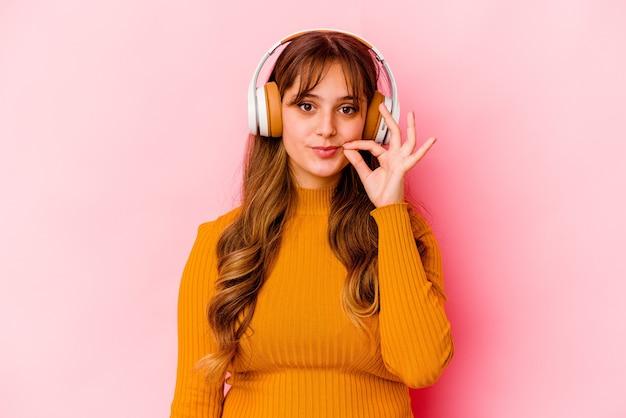 Jovem mulher caucasiana ouvindo música com fones de ouvido isolados