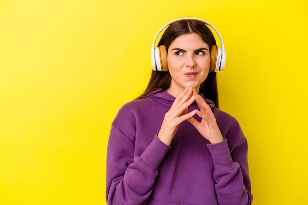 Jovem mulher caucasiana, ouvindo música com fones de ouvido na rosa, inventando o plano em mente, criando uma ideia.