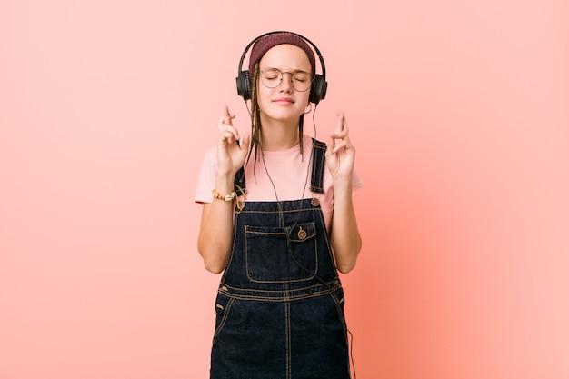 Jovem mulher caucasiana, ouvindo música, cruzando os dedos por ter sorte