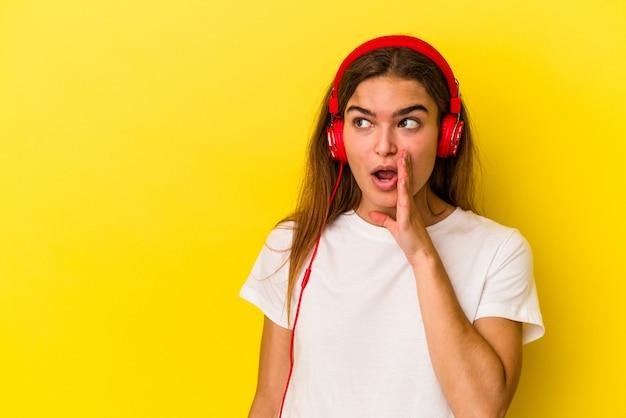 Jovem mulher caucasiana, ouvindo música isolada em fundo amarelo, está contando uma notícia secreta de travagem e olhando para o lado