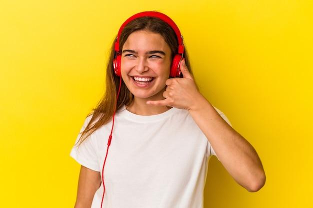 Jovem mulher caucasiana, ouvindo música isolada em fundo amarelo, mostrando um gesto de chamada de telefone móvel com os dedos.