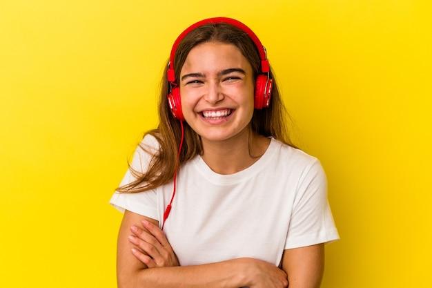 Jovem mulher caucasiana, ouvindo música isolada em fundo amarelo, rindo e se divertindo.