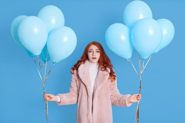 Jovem mulher caucasiana parece assustada e chocada, com a boca aberta, surpresa, segurando cachos com balões de hélio nas mãos, veste um casaco de pele rosa claro, posa contra a parede azul