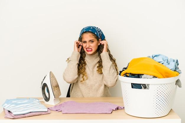Jovem mulher caucasiana passando roupas isolada cobrindo as orelhas com as mãos