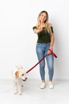 Jovem mulher caucasiana passeando com o cachorro