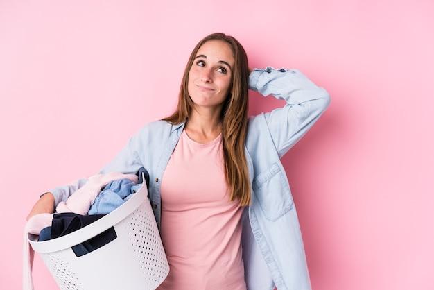 Jovem mulher caucasiana pegando roupas sujas isoladas tocando a nuca, pensando e fazendo uma escolha.
