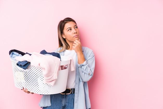 Jovem mulher caucasiana pegando uma roupa suja, olhando de soslaio com expressão duvidosa e cética.
