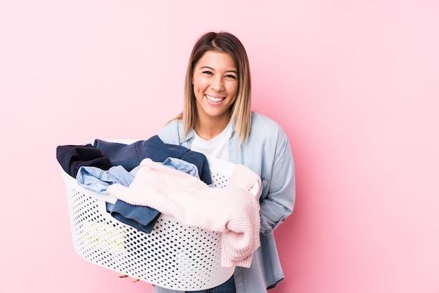 Jovem mulher caucasiana, pegando uma roupa suja, rindo e se divertindo.