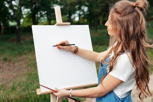Jovem mulher caucasiana, pintando na lona do lado de fora