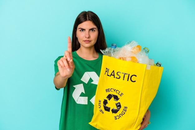 Jovem mulher caucasiana, plástico reciclado isolado em um fundo azul, mostrando o número um com o dedo.