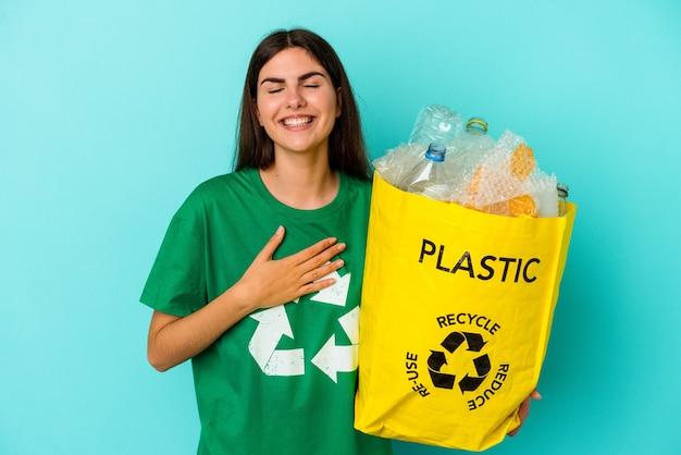 Jovem mulher caucasiana, plástico reciclado, isolado no fundo azul, ri alto, mantendo a mão no peito.
