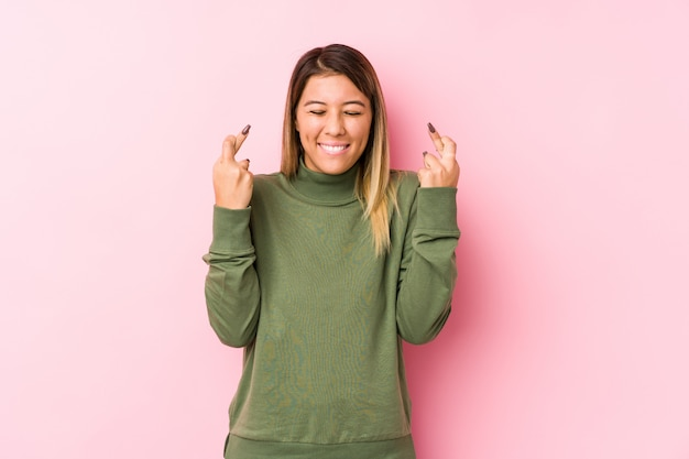 Jovem mulher caucasiana, posando de cruzar os dedos por ter sorte