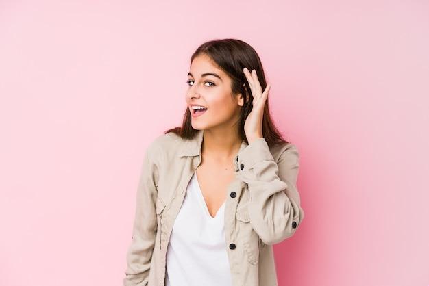 Jovem mulher caucasiana, posando de rosa, tentando ouvir uma fofoca.