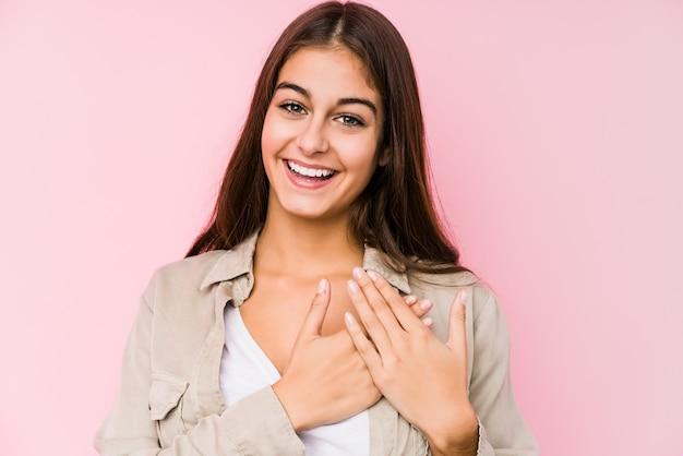 Jovem mulher caucasiana, posando em um fundo rosa rindo mantendo as mãos no coração