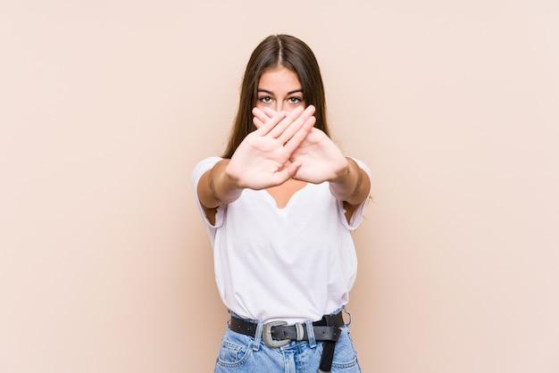 Jovem mulher caucasiana posando isolada fazendo um gesto de negação