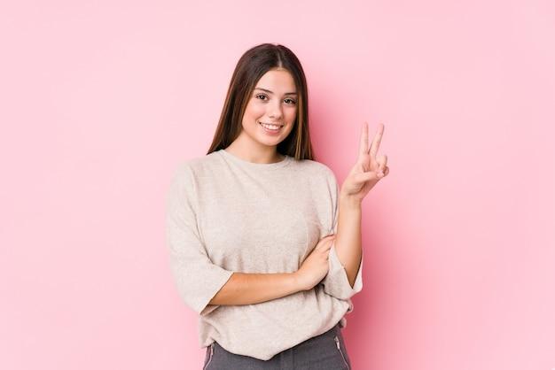 Jovem mulher caucasiana posando isolado mostrando o número dois com os dedos