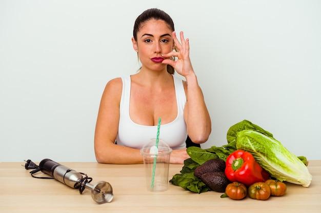 Jovem mulher caucasiana, preparando um smoothie saudável com legumes com os dedos nos lábios, mantendo um segredo.