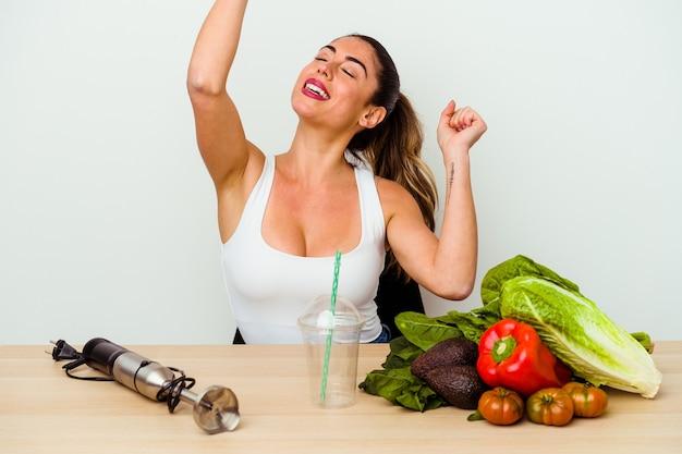 Jovem mulher caucasiana preparando um smoothie saudável com legumes, comemorando um dia especial, pula e levanta os braços com energia.