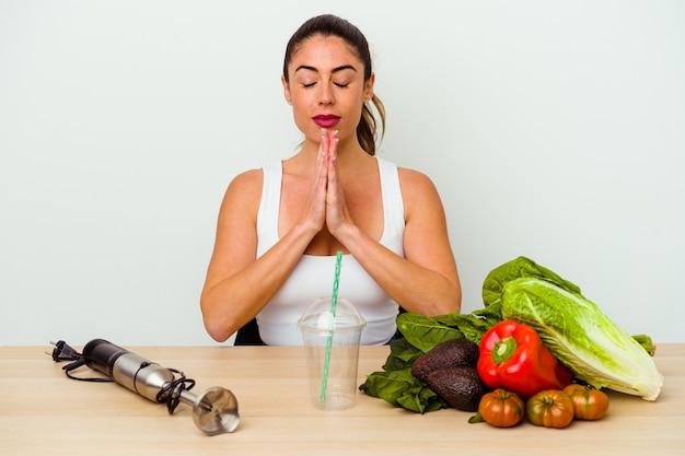 Jovem mulher caucasiana, preparando um smoothie saudável com legumes de mãos dadas perto da boca, ora de mãos dadas, sente-se confiante.