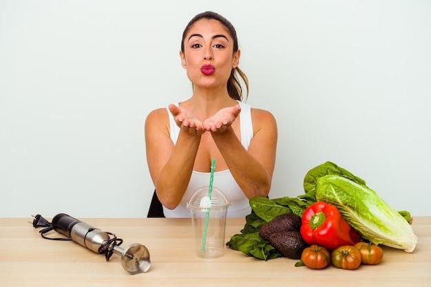 Jovem mulher caucasiana preparando um smoothie saudável com legumes, dobrando os lábios e segurando as palmas das mãos para enviar beijo no ar.