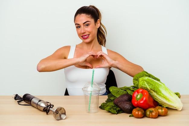 Jovem mulher caucasiana, preparando um smoothie saudável com legumes, sorrindo e mostrando uma forma de coração com as mãos.